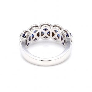 Back view of ring. A simple white gold band leads to a five stone setting that has five oval cut sapphires surrounded by pave diamond halos.