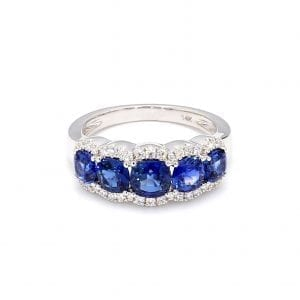 Front view of ring. Five round sapphires are set along the front half of a simple white gold band framed by pave diamond scalloped edges.