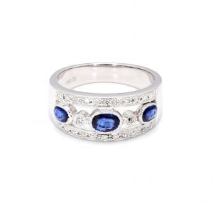 Front view of this ring with a thick white gold band, the center front has cut outs with a row of alternating bezel set oval sapphires and round diamonds. The top and bottom bands of the front half of this ring is accented by pave diamonds.