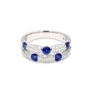Front view of ring. Two rows of diamonds and sapphires are offset from each other. The top row has three round sapphires with pave diamond stations in between each. The second row has three pave diamond stations with two sapphires in between each.