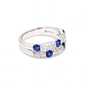 45 degree angle of ring. Two rows of diamonds and sapphires are offset from each other. The top row has three round sapphires with pave diamond stations in between each. The second row has three pave diamond stations with two sapphires in between each.