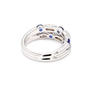 135 degree angle of ring. A double white gold shank attaches to the setting of double rows of pave diamond stations and round sapphires offset from each other.