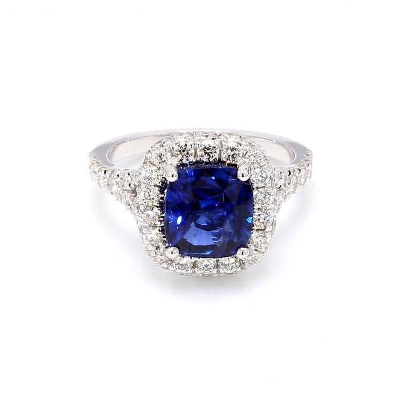 Front view of ring. A center cushion cut sapphire is surrounded by a halo of pave diamonds with additional diamonds set halfway down a split shank.