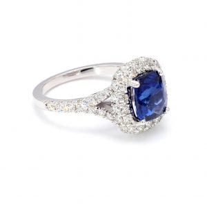45 degree view of ring. A center cushion cut sapphire is surrounded by a halo of pave diamonds with additional diamonds set halfway down a split shank.