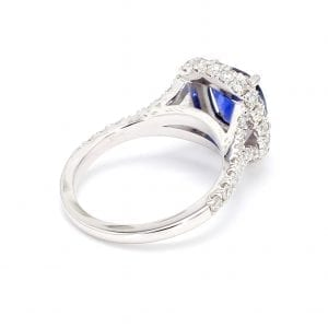 135 degree angle of ring. A white gold shank with diamonds set halfway down leads to a setting for a cushion stone. In this setting a center cushion cut sapphire is surrounded by a halo of pave diamonds.