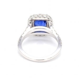 Back view of ring. A white gold shank with diamonds set halfway down leads to a setting for a cushion stone. In this setting a center cushion cut sapphire is surrounded by a halo of pave diamonds.