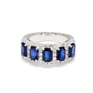 The front view of this ring shows a row of five emerald cut blue sapphires surrounded by pave diamond halos along the front of a white gold band.