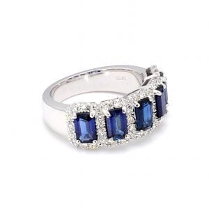 A 45 degree view of this ring shows a row of five emerald cut blue sapphires surrounded by pave diamond halos along the front of a white gold band.