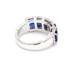 A 135 degree angle of this ring showcases a simple white gold band with 5 settings cutout to hold five emerald cut blue sapphires with pave diamond halos.