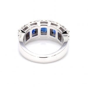 The back of this ring shows a simple white gold band with 5 settings cutout to hold five emerald cut blue sapphires with pave diamond halos along the front half.