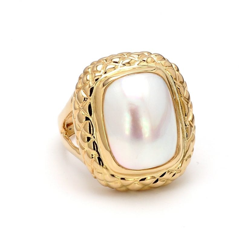 A front view of this ring shows a center elongated oval cut mabe pearl in a honeycomb detailed setting, attached to a yellow gold shank with split sides.