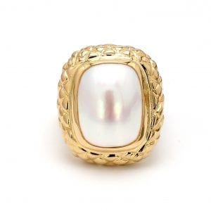 A front view of this ring showcases an elongated oval cut mabe pearl center framed by a cushion-shaped honeycomb textured setting.