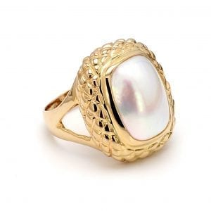 A 45 degree angle of this ring shows an elongated oval cut mabe pearl center in a cushion-shaped honeycomb textured setting, attached to a yellow gold shank with split sides.