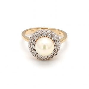 A front view of this ring shows a round, white pearl center encircled by a pave diamond halo, attached to a simple yellow gold band.