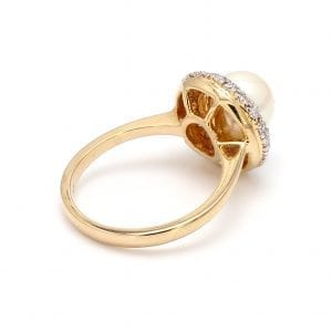 A ring is shown at a 135 degree angle. A round, white pearl center is encircled by a pave diamond halo, attached to a simple yellow gold band. Shows off a round setting with cutouts.
