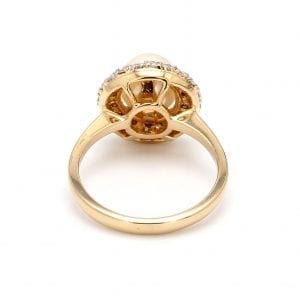 The back view of this ring shows a simple yellow gold band attached to a round setting that has cutouts, the setting holds a center pearl with a pave diamond halo.