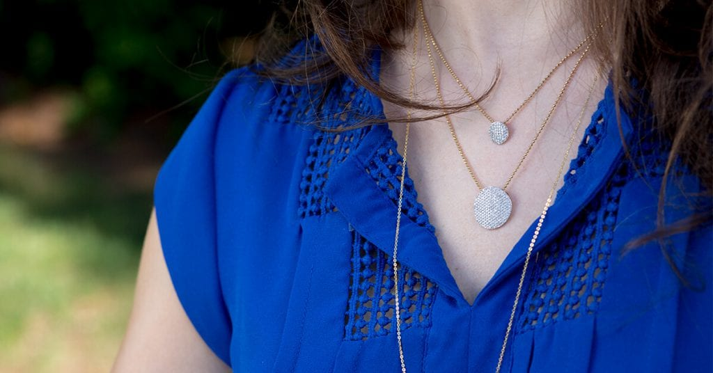 Lady in a blue shirt wearing a Phillip's House Diamond Necklace