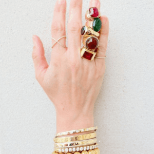 gold bracelets and gold and red and green stone rings on model