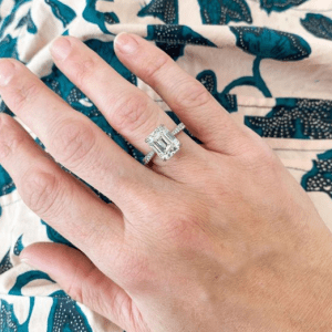 diamond ring on hand with colorful background