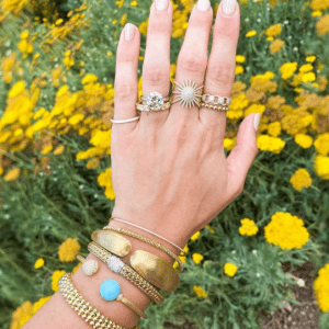 gold and diamond rings and bracelets on model with floral background