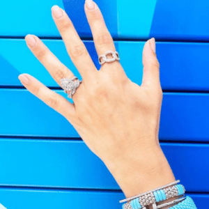 turquoise, silver, and diamond rings and bracelets on blue background
