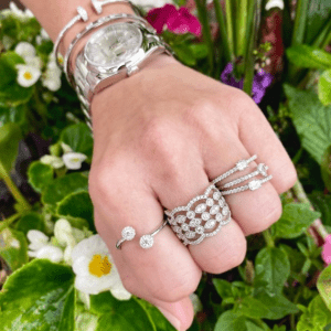 silver watch, bracelets, and rings on model with floral background