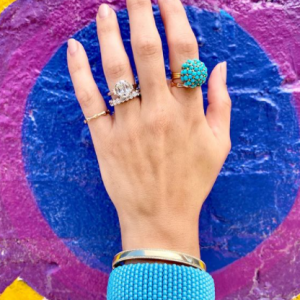 gold and turquoise rings and bracelets on model with colorful background