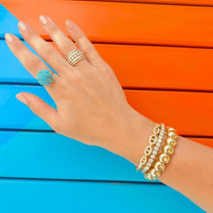 gold and turquoise and diamond bracelets on rings on model with blue and orange background