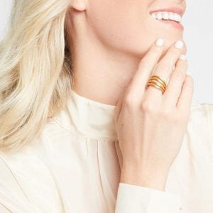 A textured, gold plated shank splits off into four bands along the front half of this ring. The ring is being modeled on the middle finger of a laughing woman who is lightly touching her chin.