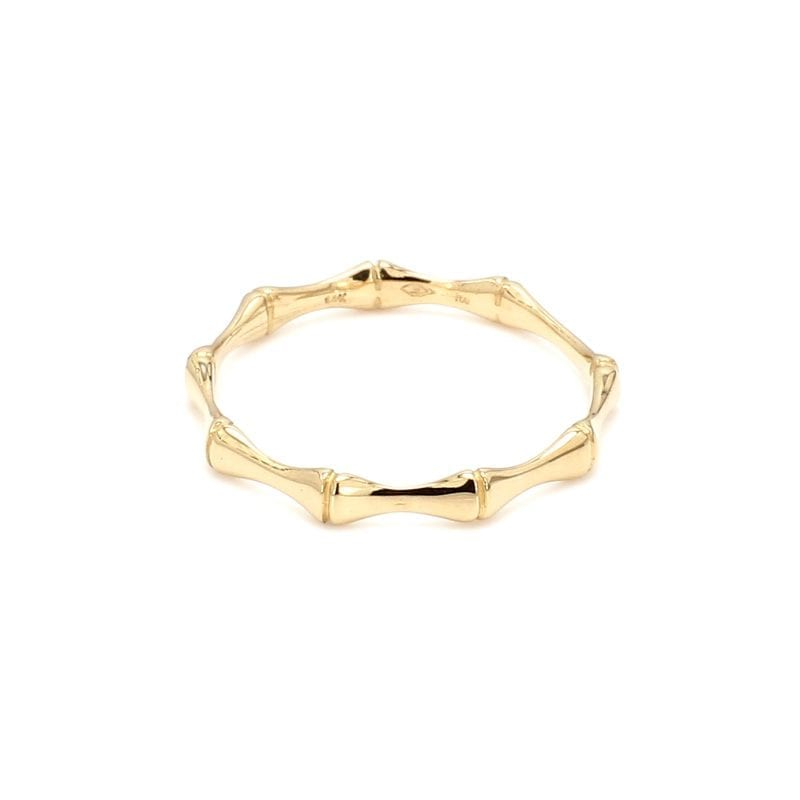 Front view of ring. A polished yellow gold band is made up of small bamboo motif stations connected all the way around the ring.