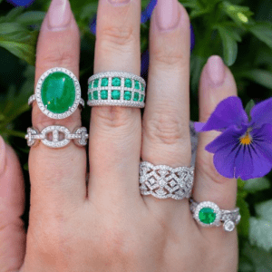 emerald and diamond rings on model