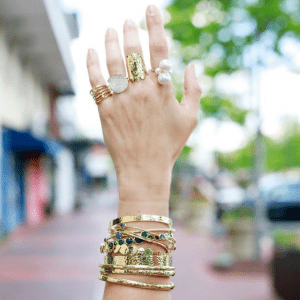 rings and stack of gold bracelets on model