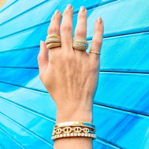 gold and diamond bracelets and rings on model with blue background