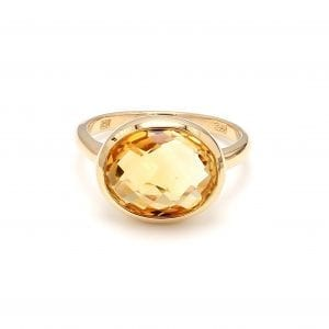 Front view of ring. A polished yellow gold shank boasts a briolette cut oval citrine, set east to west.