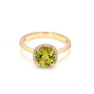 Front view of ring. A center, light green peridot is surrounded by a halo of diamonds, complimented by a polished yellow gold shank.