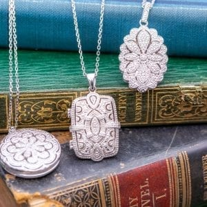 silver and diamond lockets draped over stack of three vintage books
