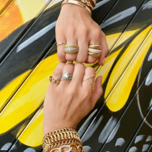 gold and diamond bracelets and rings on model with black and yellow background