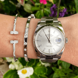 silver watch and bracelets on floral background