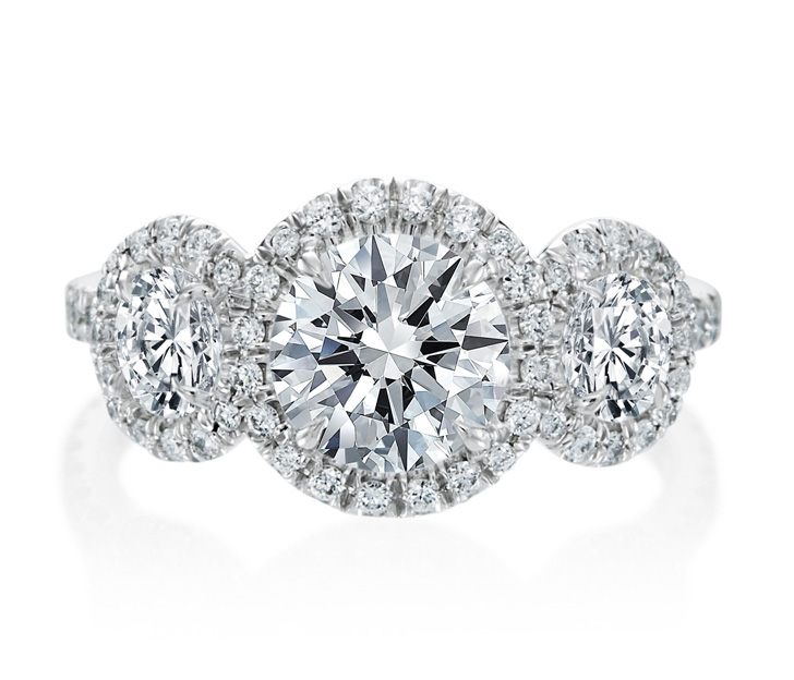 Engagament ring view with three round diamonds each with thin diamond halo on white background