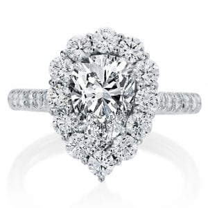 diamond engagement ring with pear cut diamond center and round diamonds in the halo. face in view with white background
