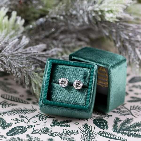 Two diamond earrings in a green box
