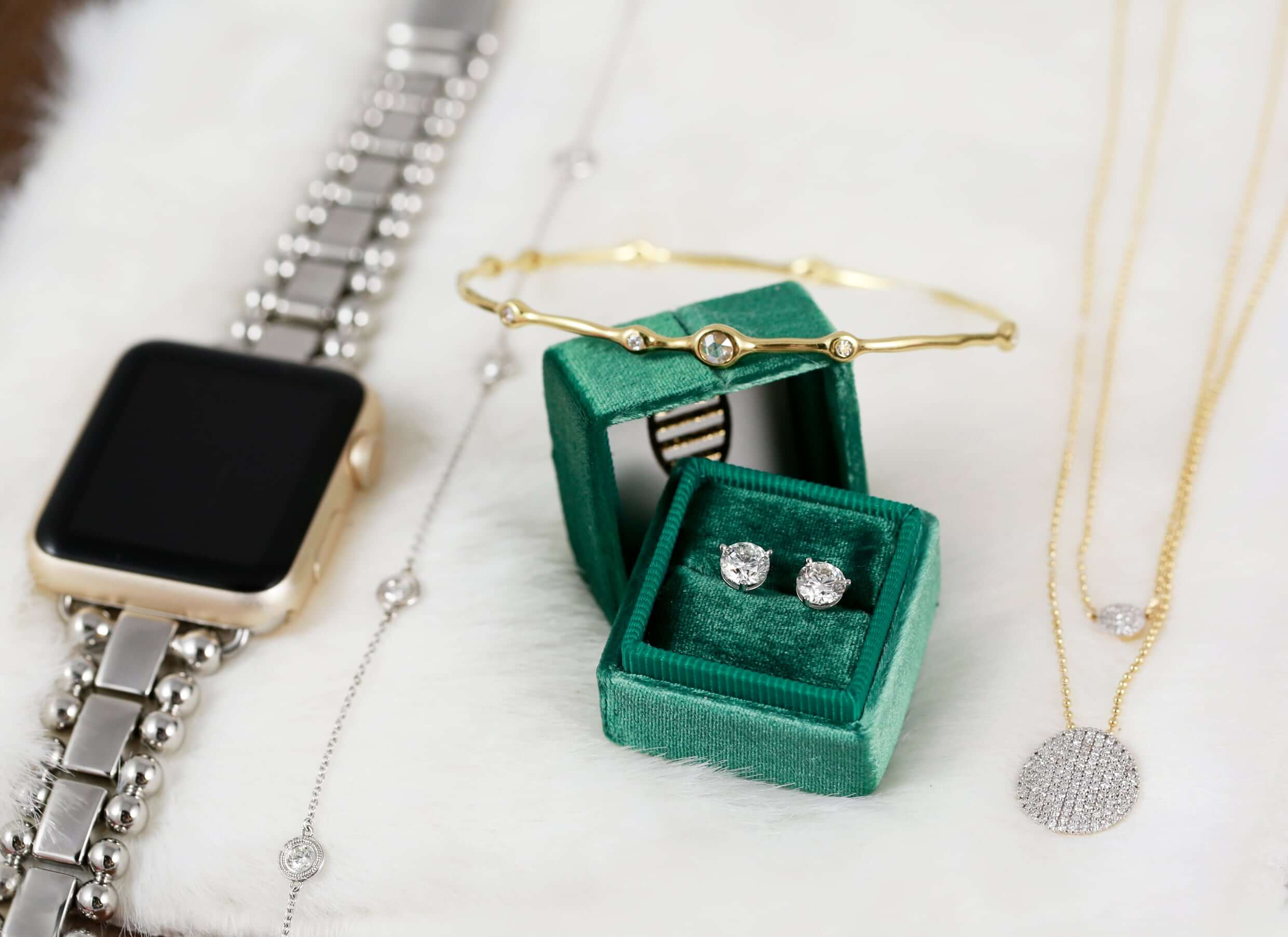 Styled image of watch, necklace, and earrings