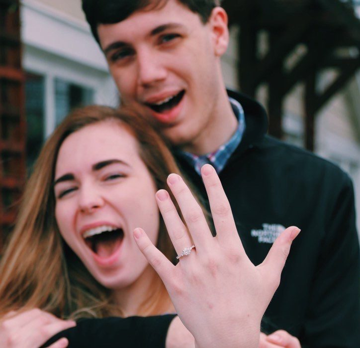 Excited couple with hand showing off engagement ring. Hannah and Michael Engagement Ring Testimonial.