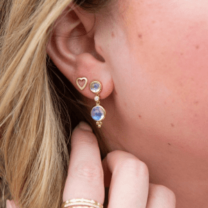 gold heart earrings and gold and blue earrings and gold rings on model