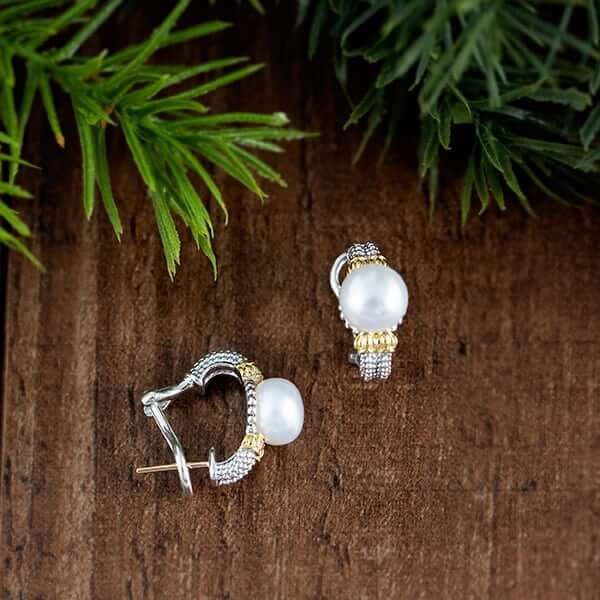 Silver and pearl earrings on a wood table