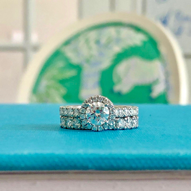 Engagement Rings and Wedding Band on blue surface. Nancy B.'s New Rings
