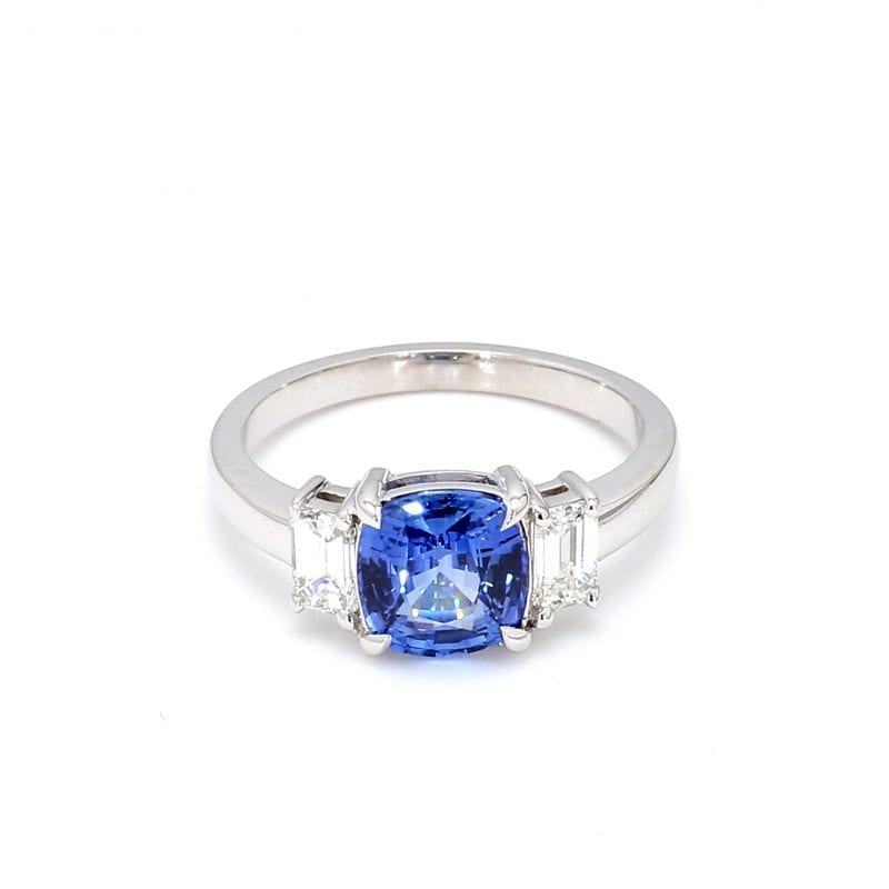 Front view of ring. A center cushion-cut sapphire is accented with an emerald cut diamond on either side, attached to a simple white gold band.