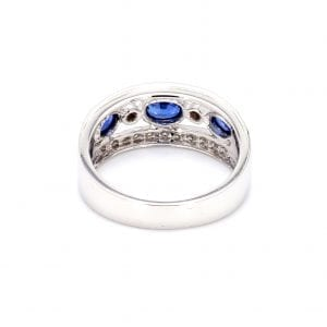 Back of this ring with a thick white gold band with cutouts in the center and cutouts in the metal from the bezel set row of alternating oval sapphires and round diamonds. Indents in the top and bottom band of the front half of this ring where the pave diamonds are set.