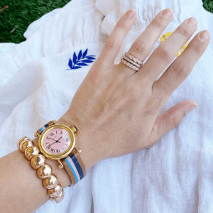 watch, gold bracelet, and gold and diamond rings on model