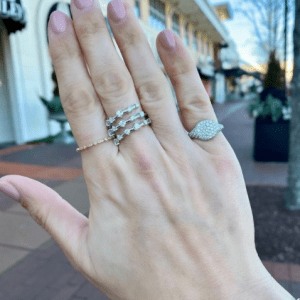 two diamond and silver rings and one gold and diamond ring on model